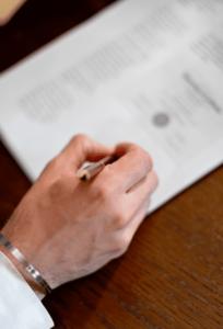 Männerhand unterschreib zertifizierten Vertrag